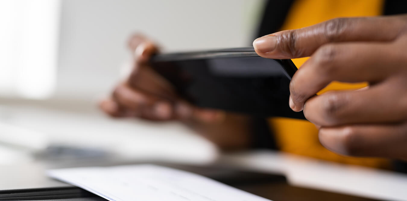 photo of two hands with a mobile phone taking a photo of a check for mobile deposit